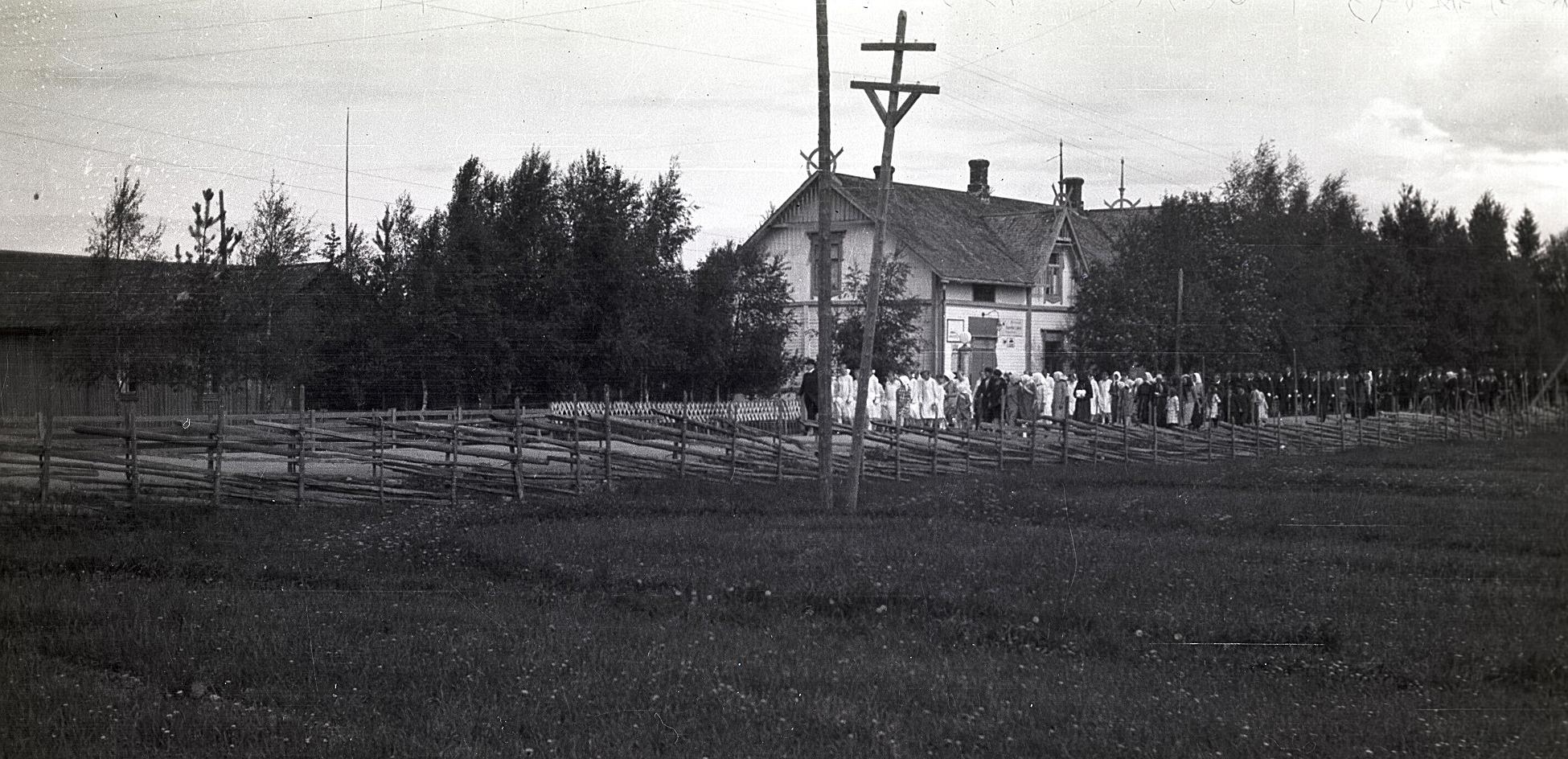 """På fotot från midsommaren 1928 ser vi den långa raden av konfirmander, som startar """"tenn fö Kaljohanas"""", alltså vid Charles Ulfves affär nere i kyrkbacken. Längs landsvägen syns en tidstypisk gärdesgård."""