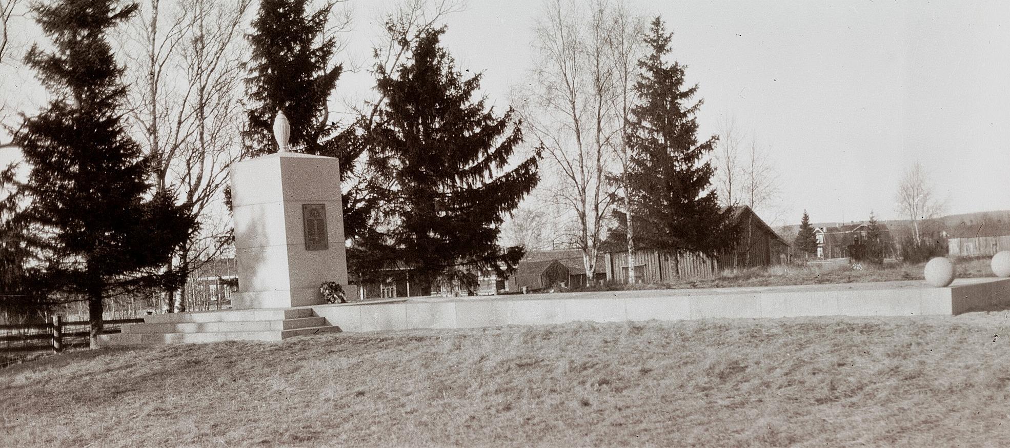 """Minnesmärket över de stupade i frihetskriget 1918 framför de granar som sågades ned 2016. Till vänster om minnesmärket syns """"Väktarinas"""" alltså Viktor Ingves och på högra sidan """"Soininenas"""" alltså Oskar Sillanpääs hus. I huset mitt i bild som kallades """"skärhuset"""" obducerades mördade, drunknade och andra osäkra fall. Långt bakom till höger skymtar den finska folkskolan och Svedar Johanas, alltså Asplunds hus."""