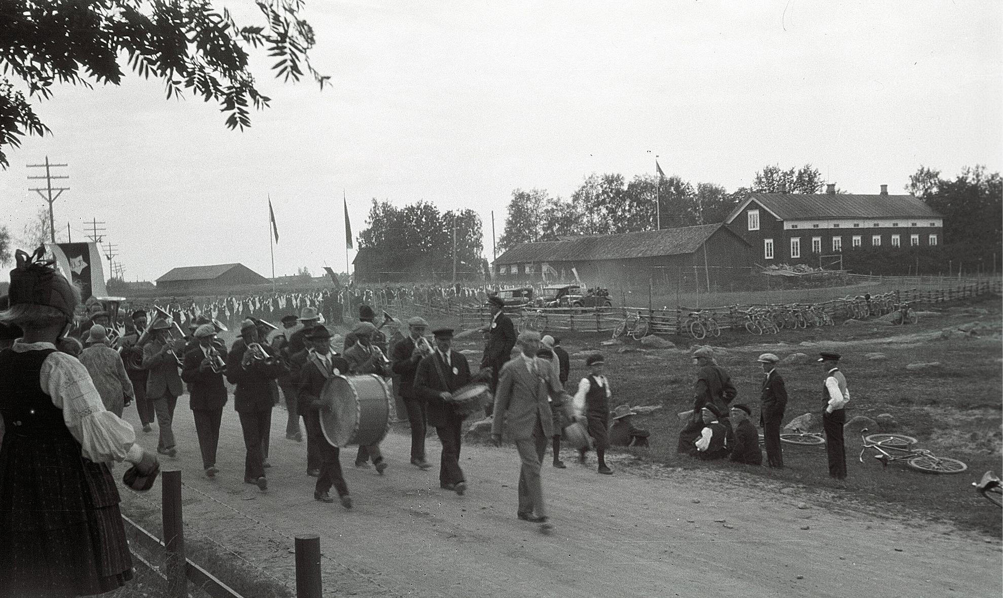 En lång rad med sångare och musikanter på väg från kyrkan till ungdomslokalen under sångarfesten i Lappfjärd 1930. Till höger syns Starkes eller nuvarande af Hällströms gård.