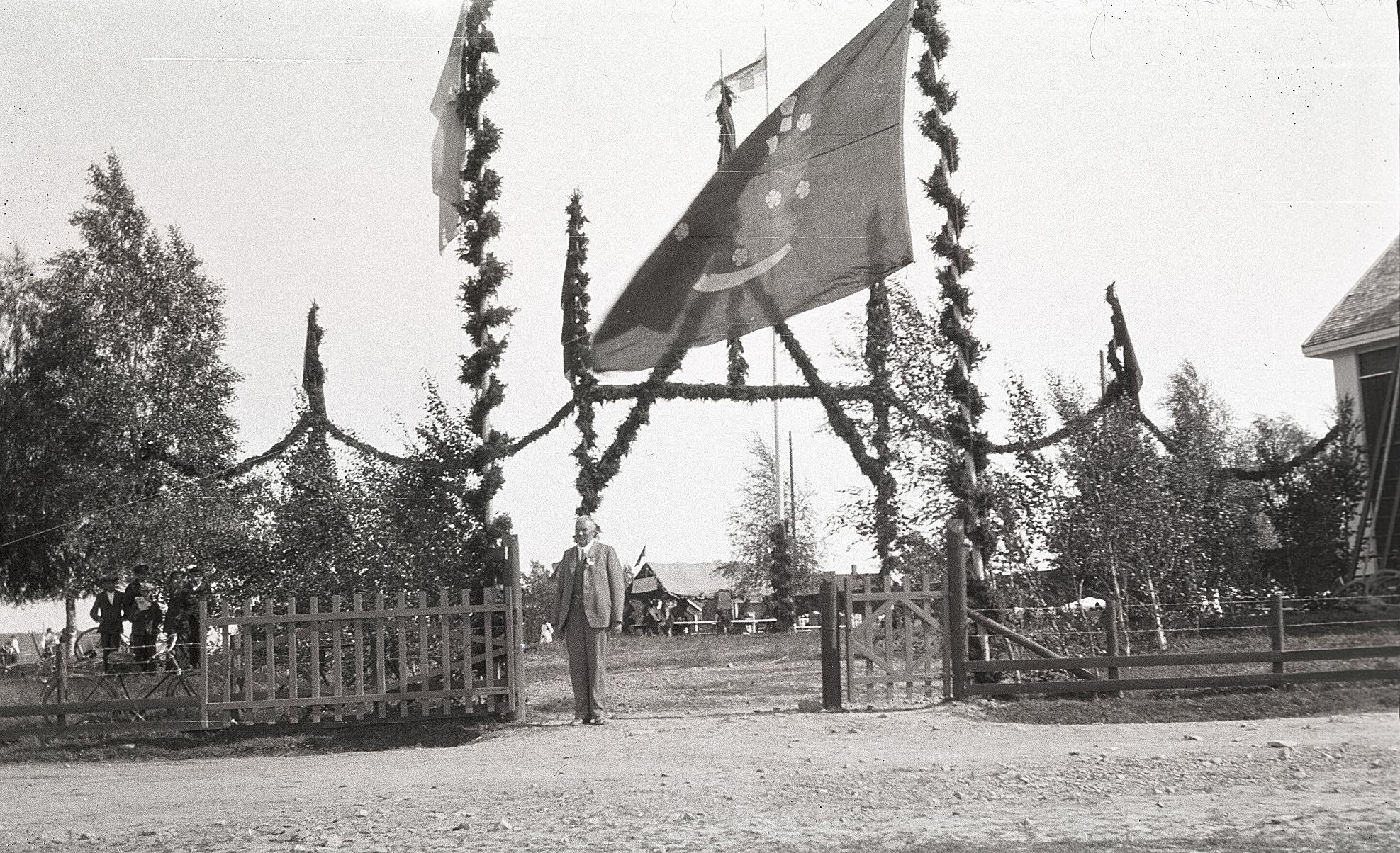 Den ståtliga porten till idrottsplanen under sångarfesten i Lappfjärd 1930. Gaveln till lokalen syns i högra kanten.