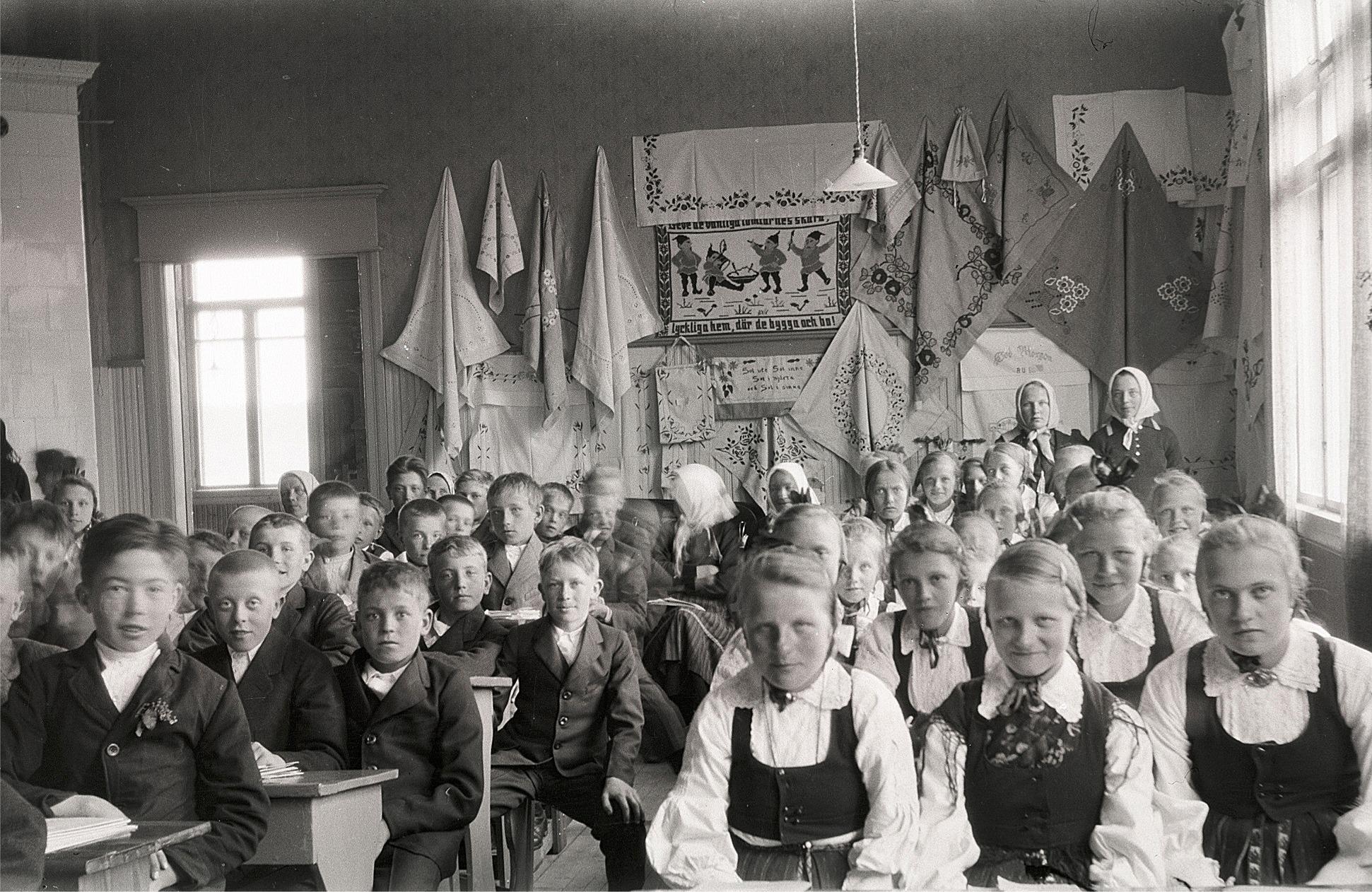 Foto från skolavslutningen 1930, där flickornas handarbeten finns upphängda på väggen. Till vänster sitter Arvo Haavisto och Karl Malm. Flickorna är Märta Skogman, Svea Ådjers, Ellen Norrholm, Elin Mangs och Alice Björses. Pojken mitt i bild med handen på knät är Valter Björknäs och bakom honom en pojke med huvudet på sned och det är Erik Storkull, senare Stens, som sedan gjorde ett stort arbete med att identifiera alla dessa Selim Björses fotografier.