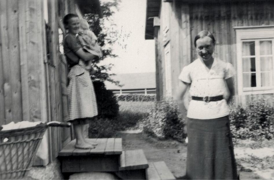 På trappan står Alina Björses med ettåriga Brita i famnen. På gården står svägerskan Signe, f. Björkman.