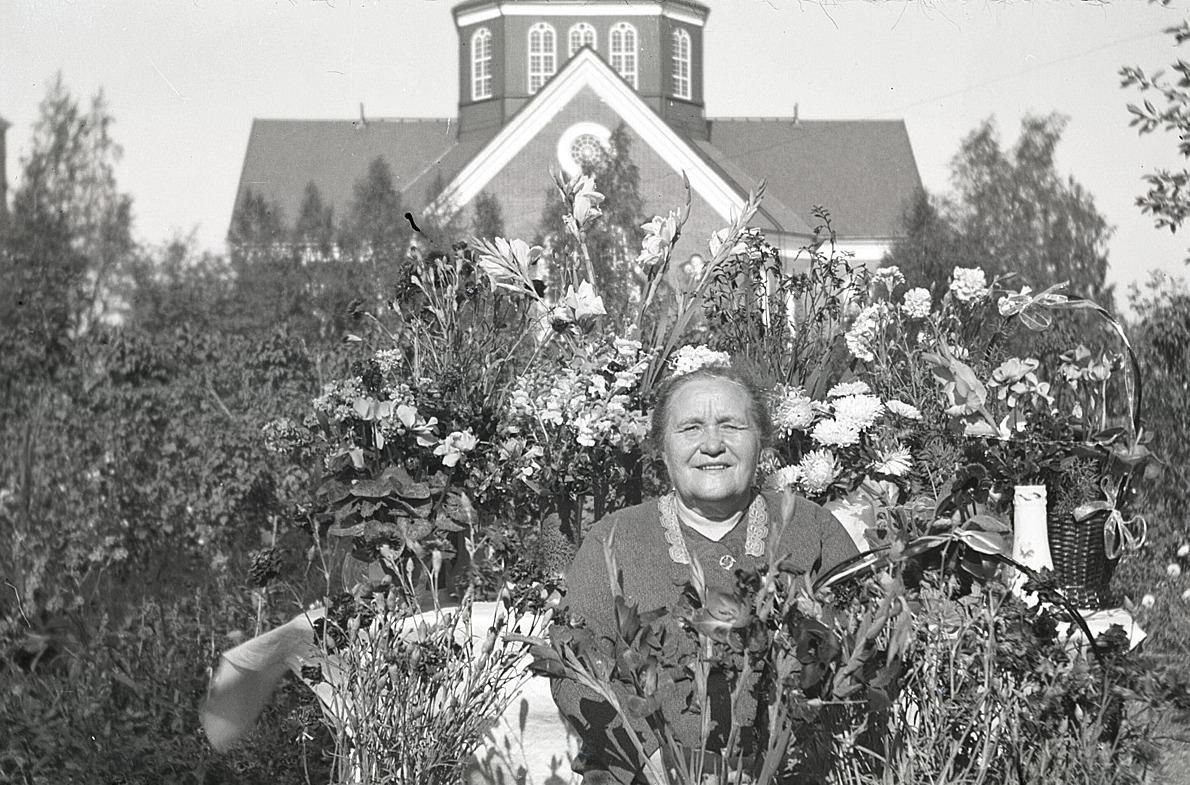 Lärarinnan Emmi Bast uppvaktades rikligt med blommor då hon fyllde 65 år och här sitter hon ute i trädgården utan lärarbostaden.