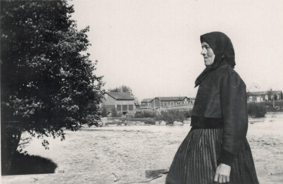 """Mina Storhannus, som kallades """"Hanås-Mina"""" på väg över till Nössidon. Mitt i bild Holmkvarnen och till höger syns Ingves nämndinas lillstuguraden med port."""