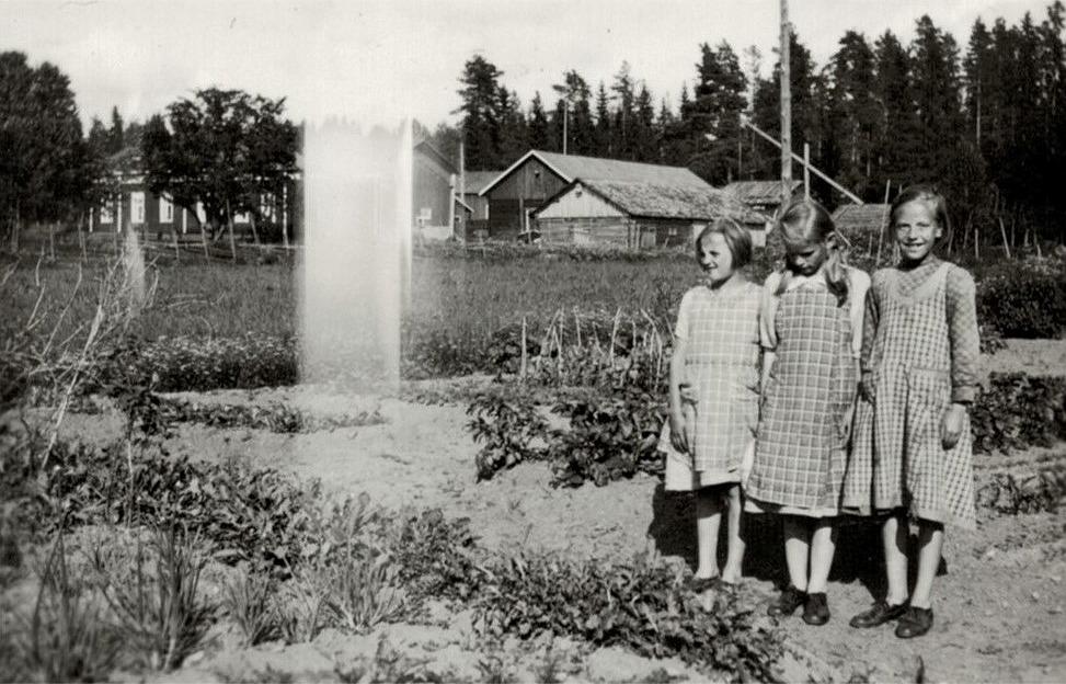 Tre korsbäckflickor står vid Sylvia Liljedahls (f.1928 senare Stenlunds) trädgård. Stenlunds ståtliga gård i bakgrunden.