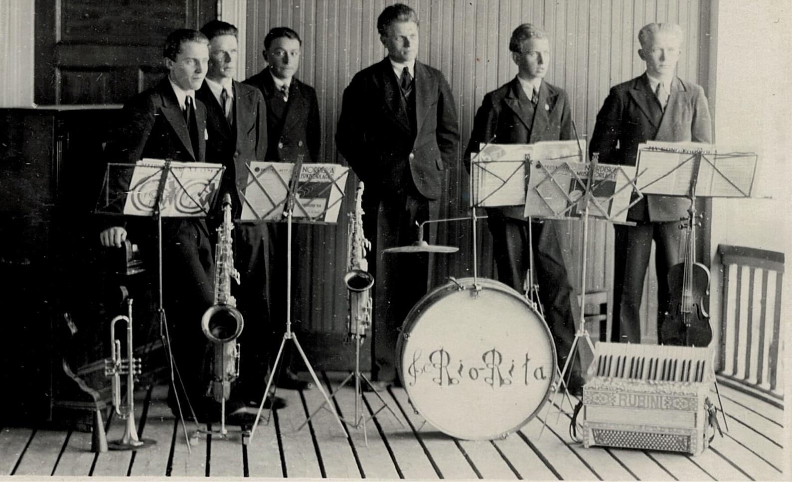 Mellan åren 1932 till 1939 så var Rio-Rita den absolut populäraste dansorkestern i Syd-Österbotten. Från vänster Åke Knus, som spelade piano, Emil Björknäs på tenorsaxofon, Birger Lillhannus på trumpet, Lennart Knus på altsaxofon, Elis Knus på dragspel och Otto Fröberg på fiol och dom står på lokalens uteveranda i Lappfjärd. Från början hade orkestern också flera andra medlemmar, bland annat Valter Enlund, Torsten Pärus, Sigurd Brogård, Valter Brogård och Egil Appel.