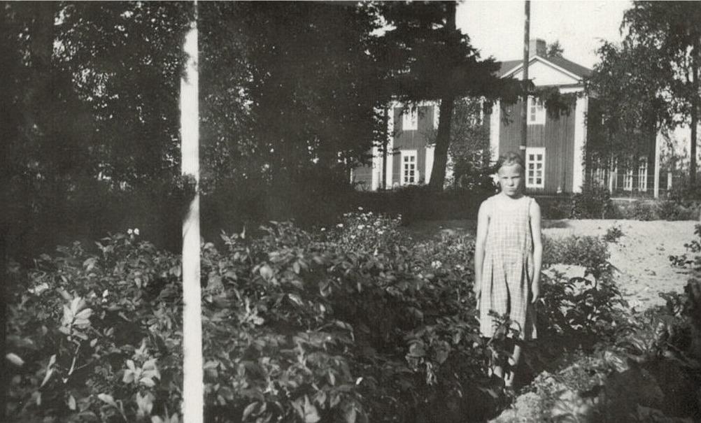 Saga Korsbäck (1928-2007 som sedan gifte sig med Einar Rönngren) i hemträdgården i Korsbäck, där skolan syns i bakgrunden.