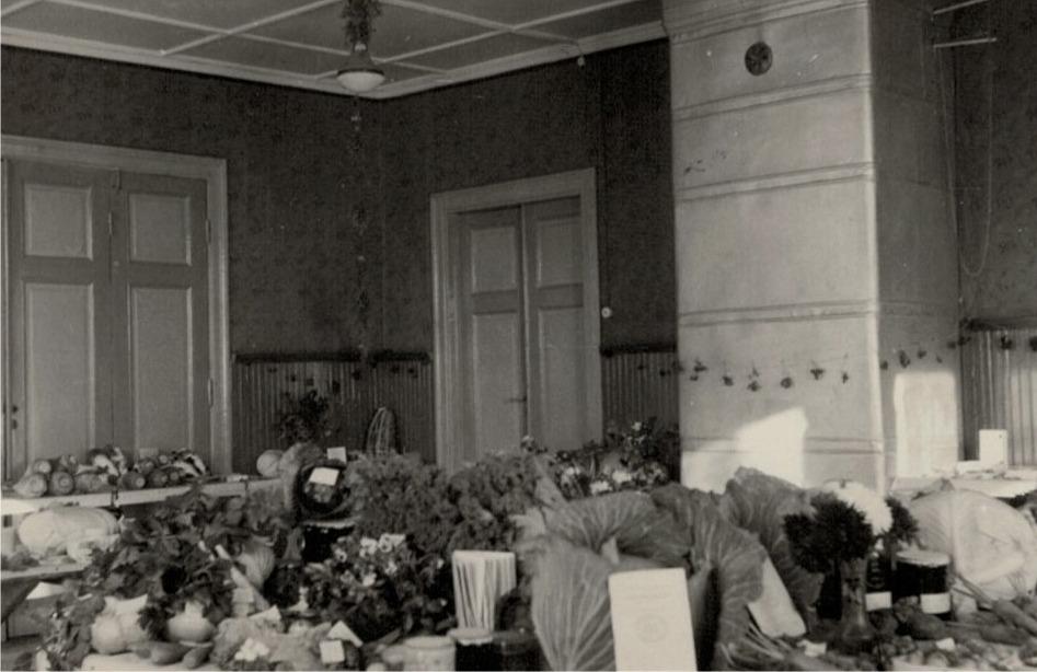 Utställning av lantbruksklubbens produkter i södra folkskolans lilla sal. Genom dörrarna till vänster kommer man in i stora skolsalen.