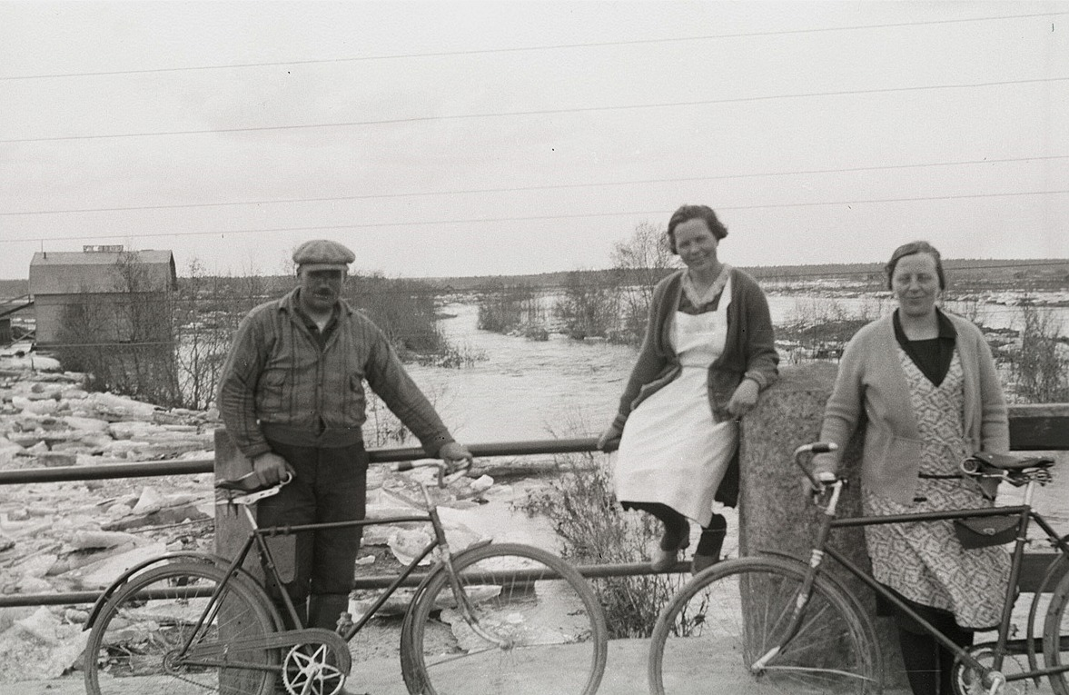 """Här står Emil Ekman, Ines Hannus och Signe Nyqvist på Nybron och tittar på islossningen. Cykeln till höger tillhörde troligtvis fotografen, för knappast skulle damerna ha klarat av att köra med """"karavagne"""" med de där kläderna."""