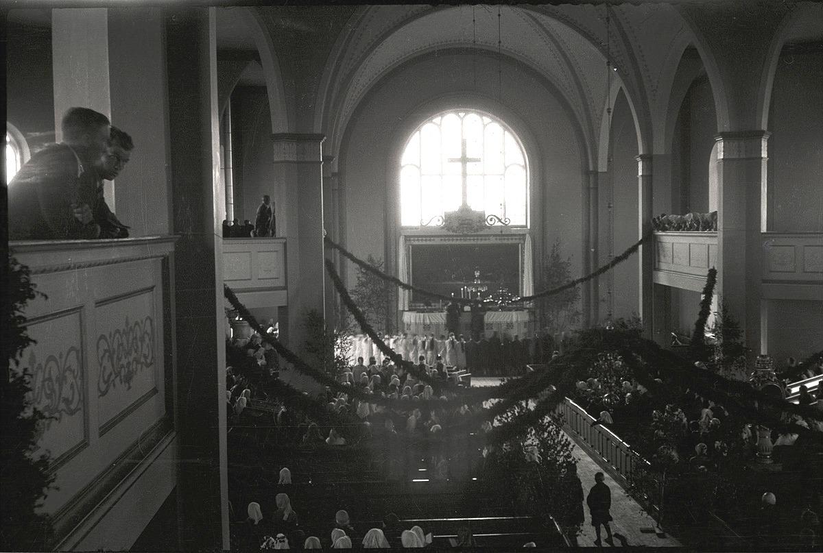 Midsommardagen 1931 var kyrkan dekorerad med björkar och enrisband. Konfirmanderna står i flera rader runt altarrundeln.