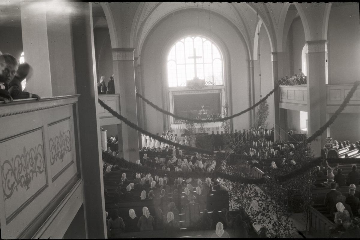 Kyrkan vackert dekorerad med enrisband och björkar.