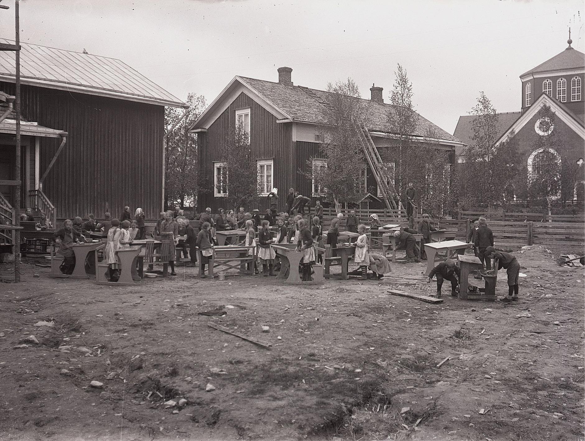 Här är det storstädning i skolan, då till och med pulpeterna förs ut på gården för att tvättas.