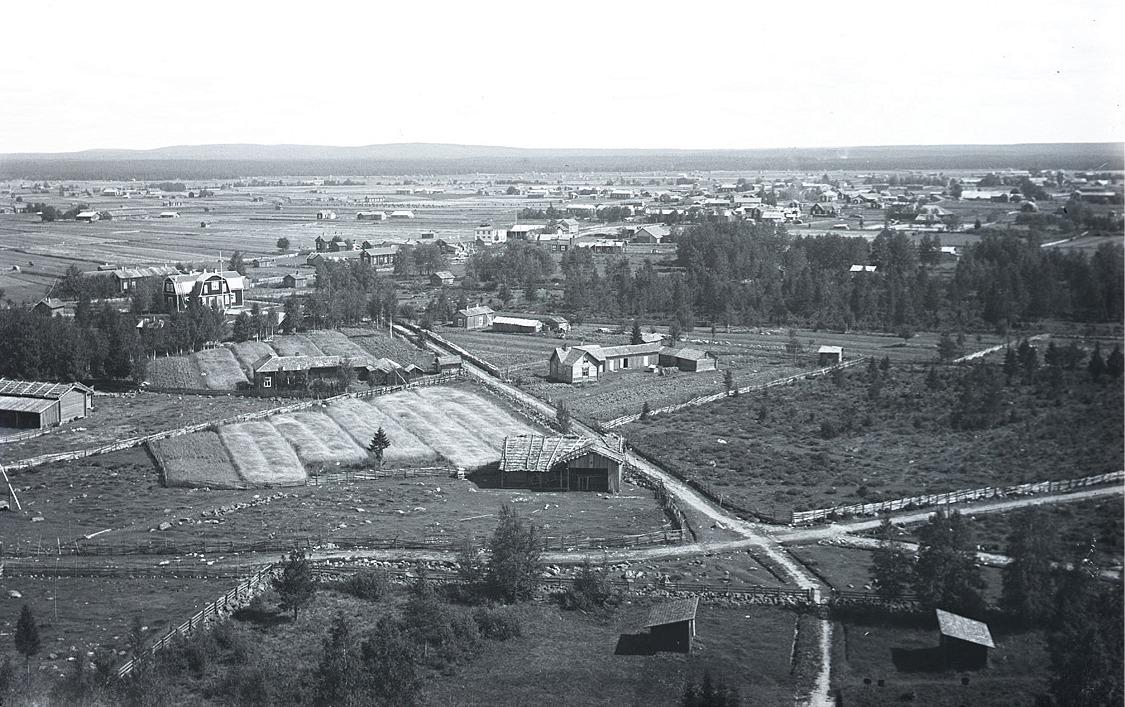 Foto från klockstapeln eller kyrktaket mot nordöst. Kyrktået och den finska folkskolan mitt i bild.
