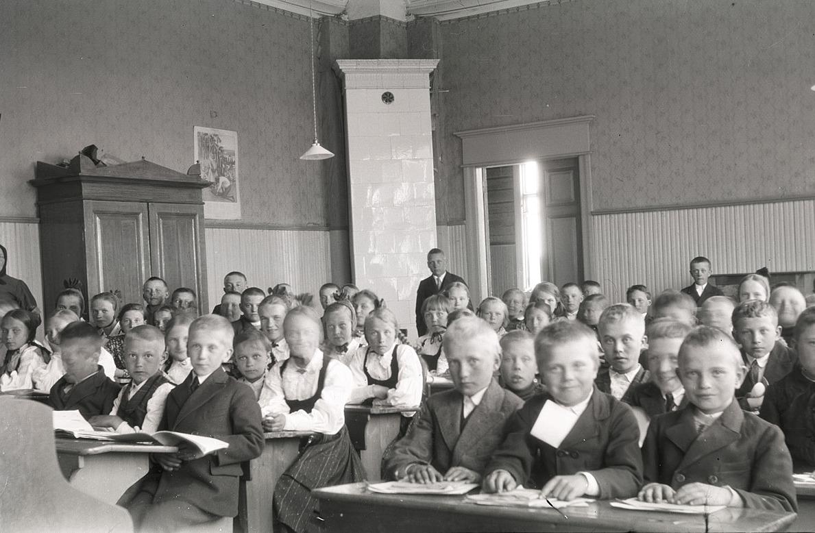 Eleverna på södra folkskolan ser alla glada ut och undra på det, då skolan är slut och sommarlovet på kommande. Läraren Selim Björses står bak i klassen.