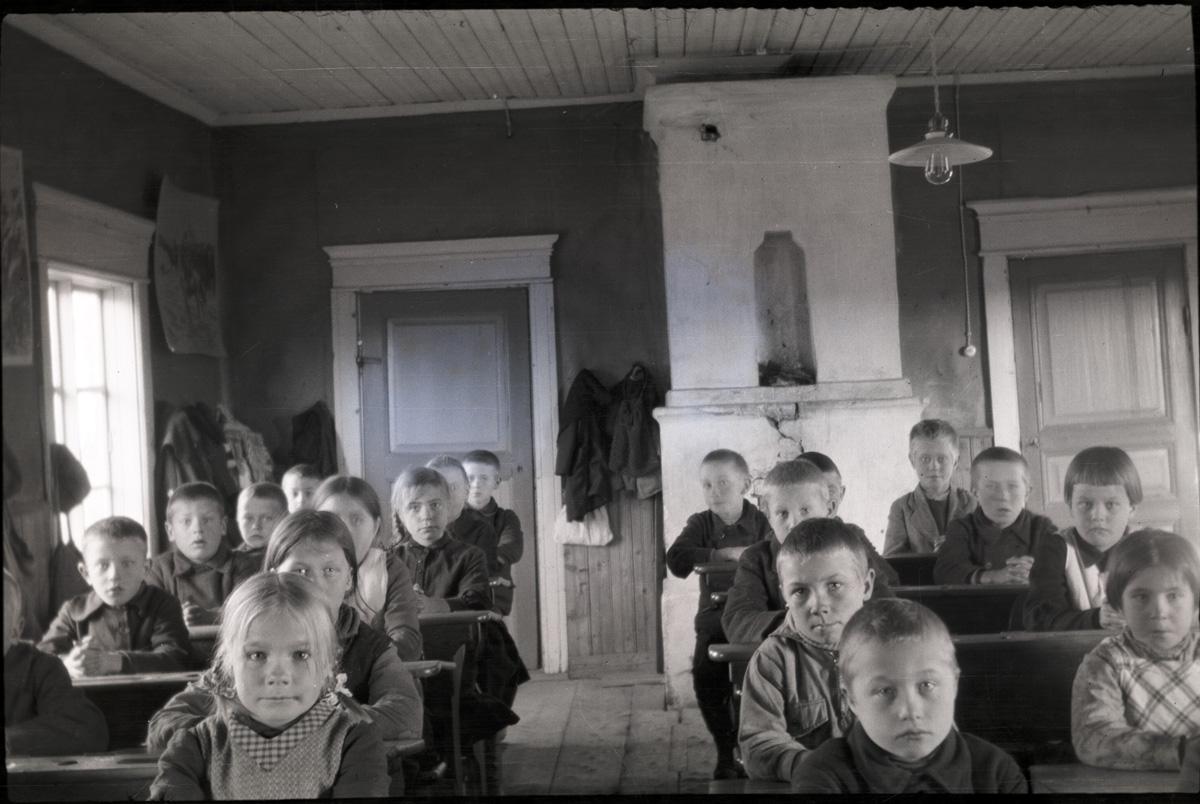 Så här satt eleverna i den gamla småbarnsskolan på Kladdbackan. Här är den sista årskursen 1932-33, sedan flyttade småskolan till södra folkskolans tillbyggnad. Dörrarna bak i salen gick in till lärarinnan Tekla Skrivars rum. Notera den speciella lampan i taket. I raden längst till vänster sitter Ingmar Nyqvist, Alfons Nyqvist, Gösta Gullmes, okänd. I följande rad mot höger sitter Rut Rosenback, Gunvor Juth, Ellen Haavisto och Elvi Lassfolk. Raden på andra sidan mittgången sitter Nils Mitts, Johan Hellman, Per Klockars, Uno Lassfolk, Birger Hellman. Längst till höger sitter Judit Hellman, Maj-Britt Granö, Gustav Hellman, okänd.