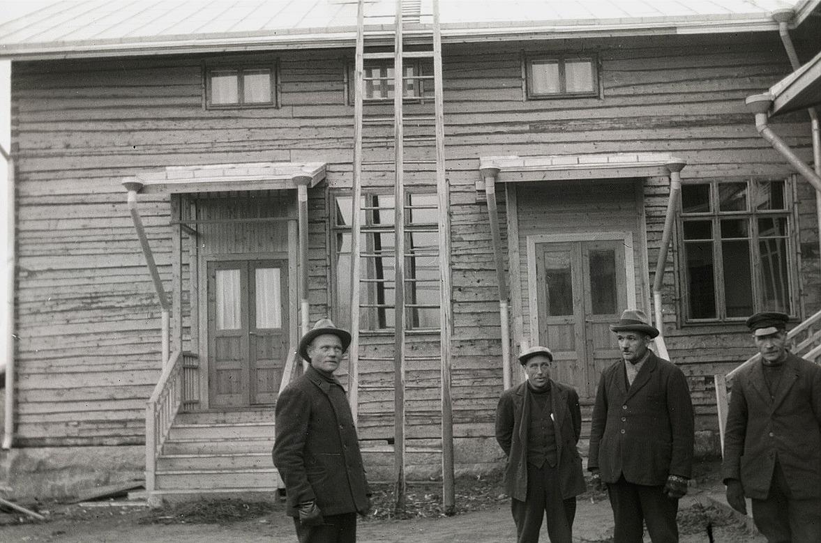 På hösten 1933 är tillbyggnaden färdig. Den vänstra ingången till lärarinnan Tekla Skrivars bostad och genom den högra dörren kom man till tamburen, en skolsal och skolköket. Till vänster står Karl Knus, entreprenören Erland Krook, sedan Emil Ekman och till höger står Viktor Rosenstedt.