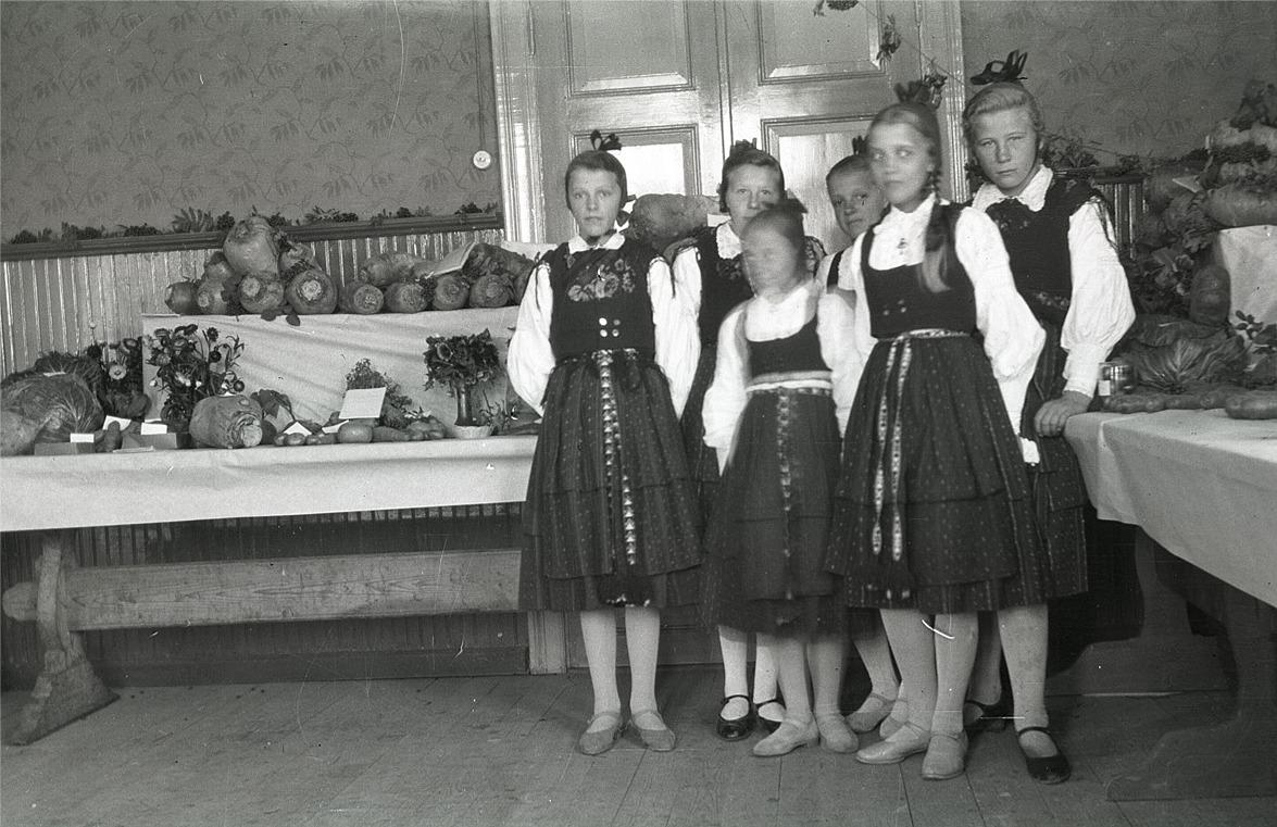 Utställning av lantbruksprodukter i skolan, där flickorna har fina folkdräkter, från vänster Svea Ådjers, Helmi Ekman, Anni Enlund, Agnes Ålgars och Elin Mangs.