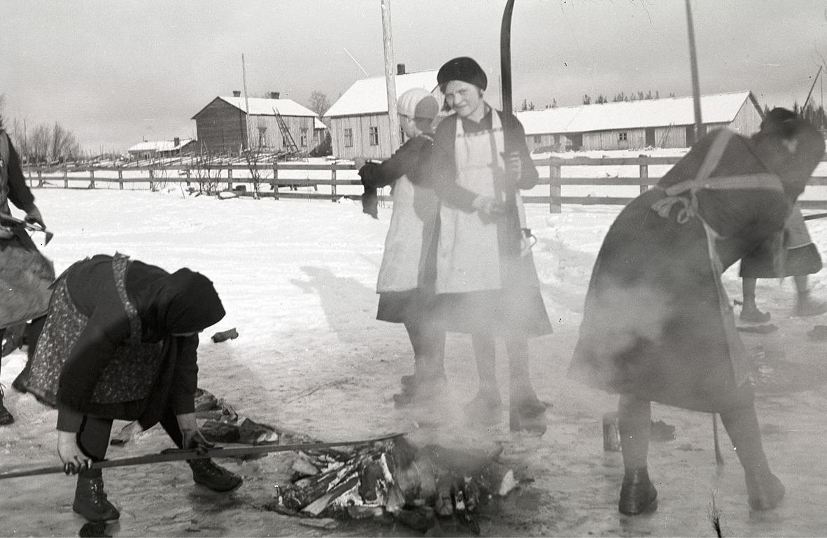 """Här håller flickorna på och tjärar skidorna på vårvintern 1934, i bakgrunden """"Gustas Kalas"""" gårdar. Flickan mitt i bild är Anni Norrholm men notera speciellt hur flickan till vänster har tjära på händerna!"""