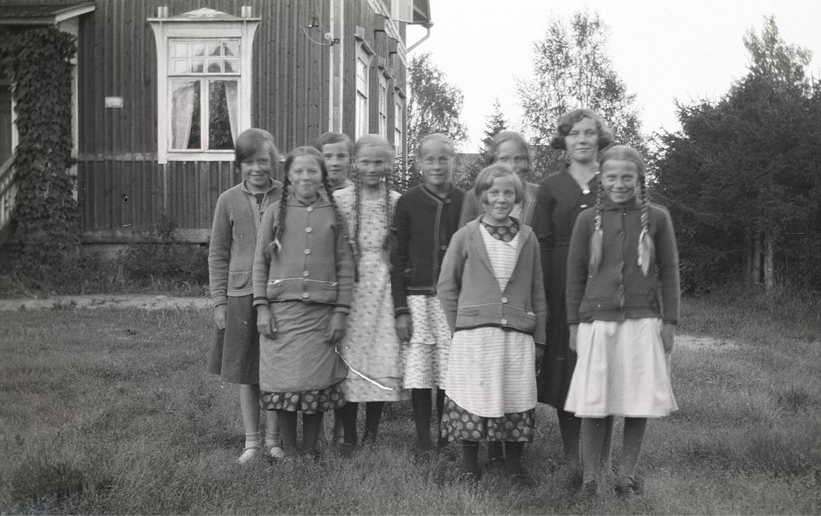 Dagsmarkflickor utanför folkskolan, från vänster Lilli Eklund, Helga Englund, Else Rosenback, Edit Agnäs, Ingeborg Krook, Anna Englund, okänd, Lilja Nordberg och Ellen Westerback.
