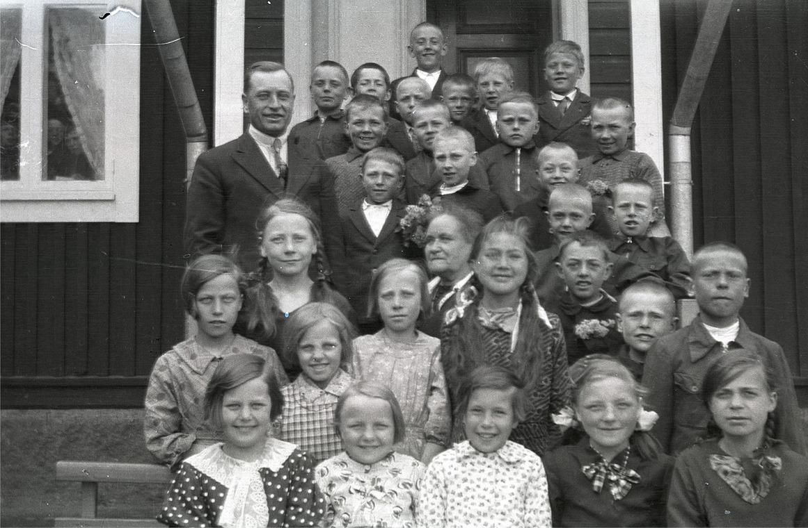 Lärarinnan Emmi Bast omgiven av skolans elever och läraren Selim Björses till vänster.