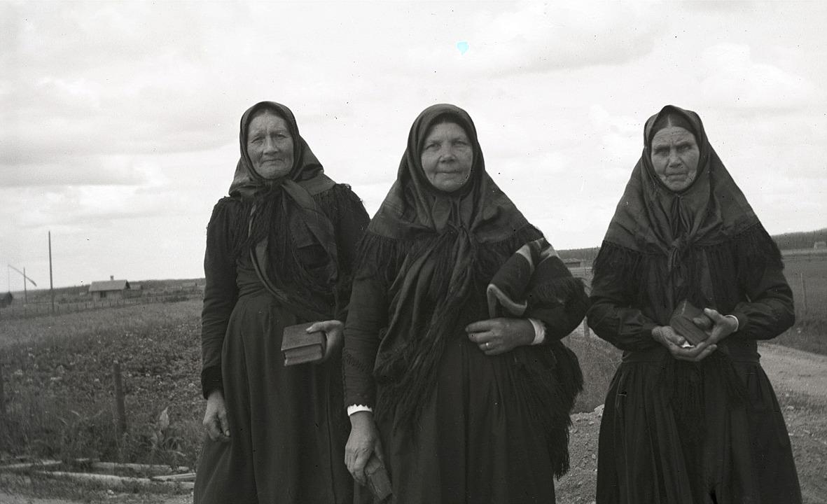 """Här visar dagsmarkkvinnorna hur man skulle vara klädd vid en nattvardsgudstjänst, från vänster """"Gåbbinas-Mina"""" alltså Vilhelmina Lillkull, sedan Bäckaas-Mari, alltså Maria Lång och till höger """"Haga-Mari"""", alltså Maria Lindberg. Skorna som de troligtvis hade haft i ena handen tog de säkerligen på fötterna, då de mötte fotografen Selim Björses på vägen."""