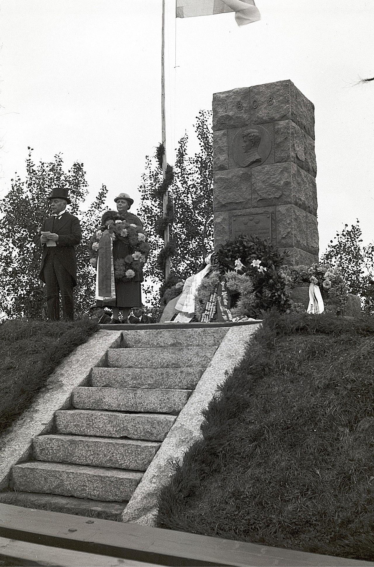 En släkting håller tal, då Wilhelm von Schwerins minnesmärke i Ömossa har avtäckts.