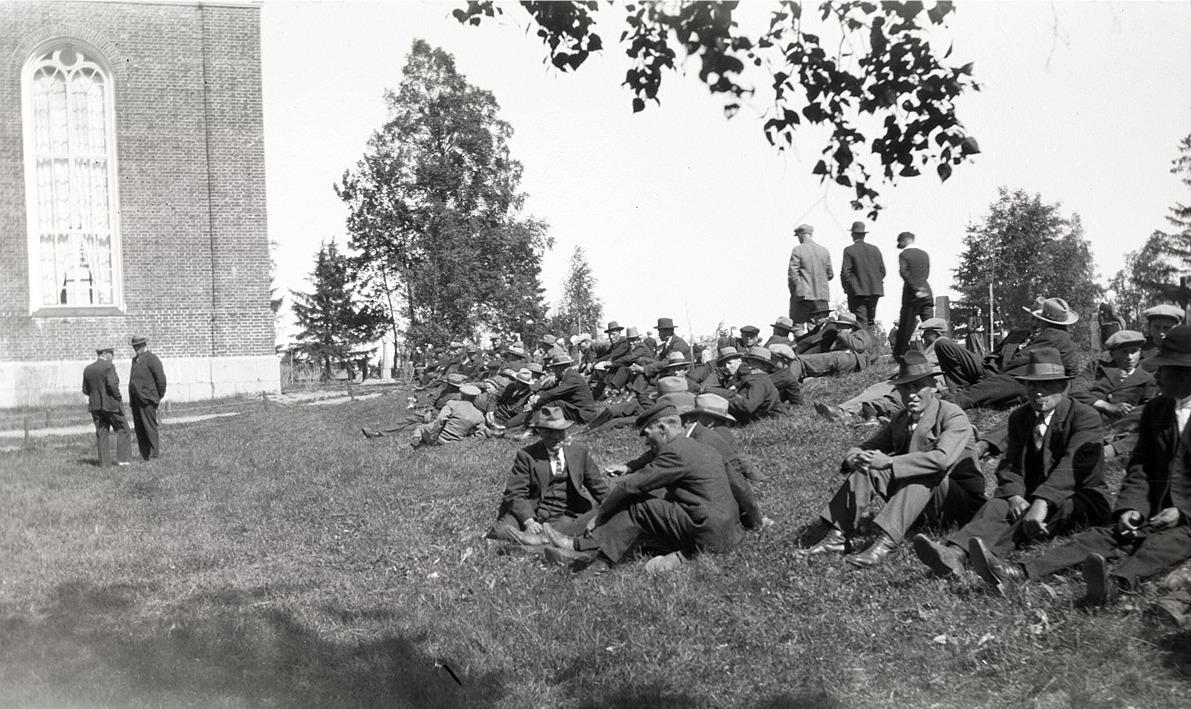 Här sitter gubbarna utanför kyrkan och njuter av sommarvärmen, på midsommardagen 1936.