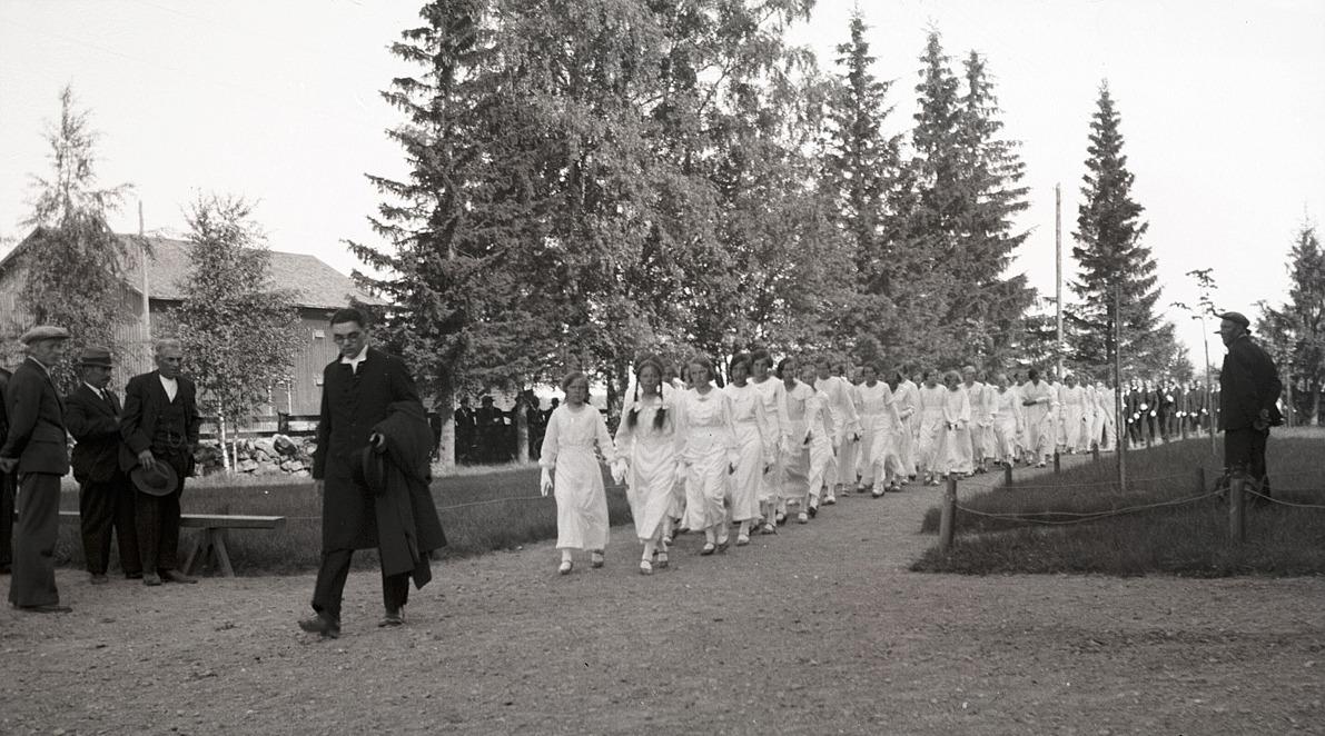 Över 100 konfirmander på väg in i kyrkan på midsommardagen 1936, flickorna i vita dräkter och pojkarna där bakom i mörka kostymer och vita handskar. Först i raden kommer systrarna Anna och Helga Englund från Dagsmark, sedan Ellen Wissander, Elin Holm, Hjördis Söderkvist, Gunni Björs och många till.