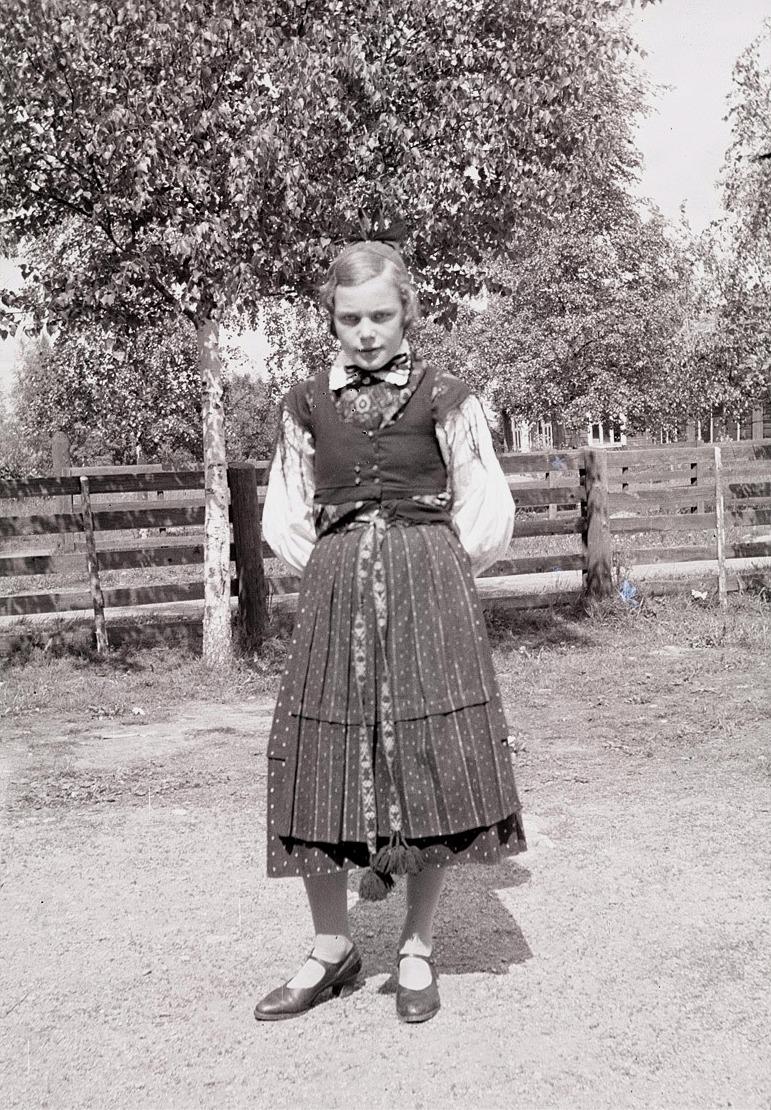 Ida Storkull på skolgården iförd Lappfjärds folkdräkt.