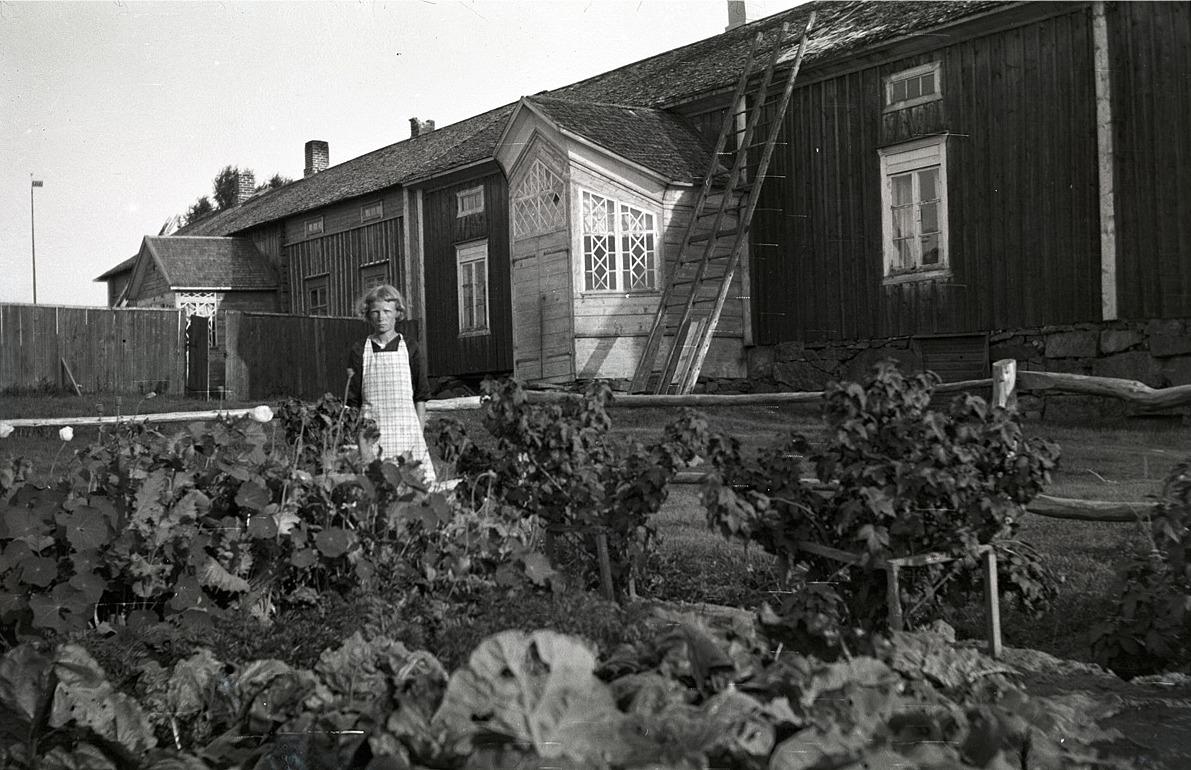 Hildur Ludén från Härkmeri som sedan gifte sig med Sigurd Ekström från Påskmark, här utanför den Byholmska gården. Se vilken gård och vilka verandor!