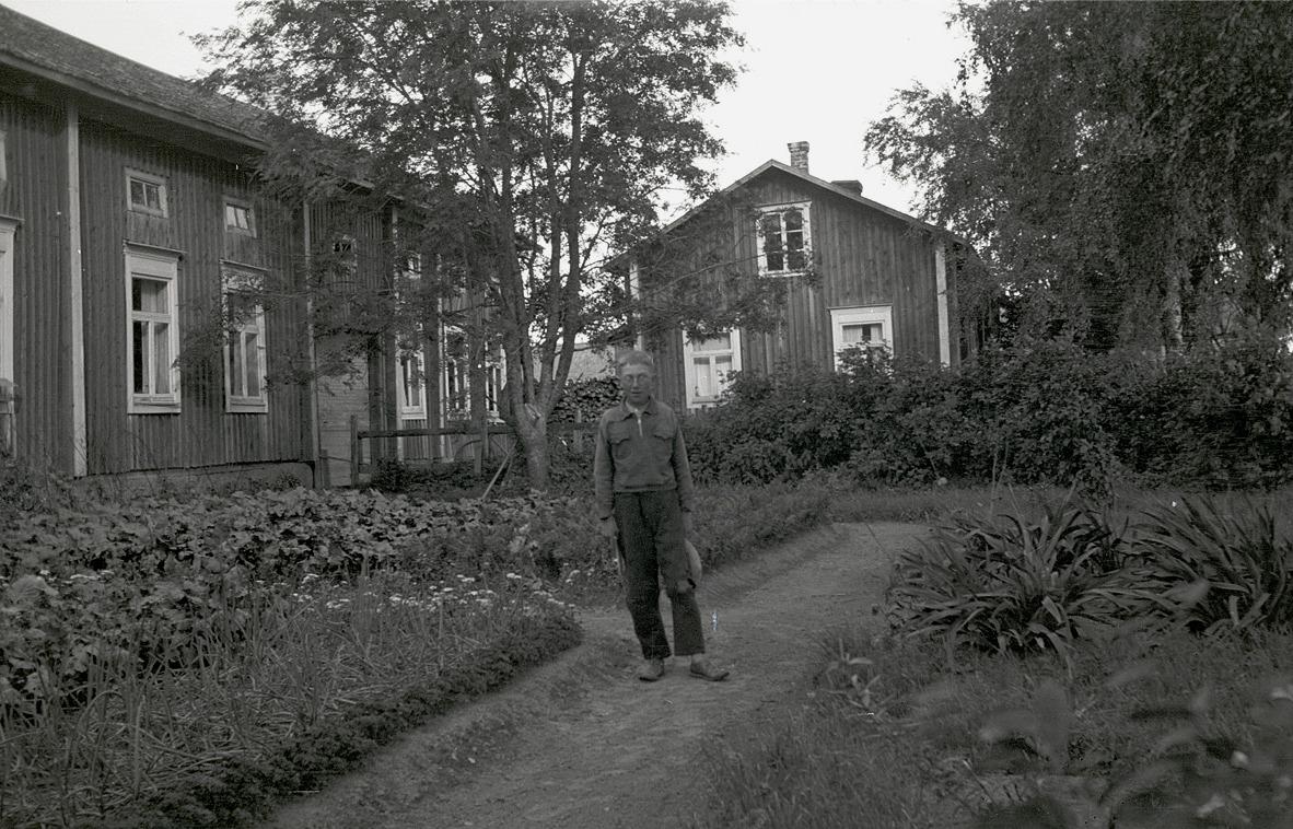 Birger Hellman står utanför hemgården, mitt bland blommor och lök.