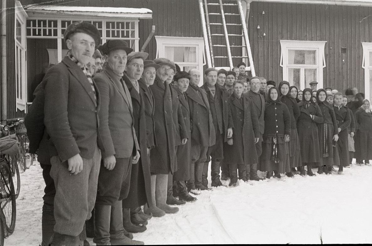 Veteranerna från frihetskriget 1918 eller deras anhöriga står här på rad utanför södra skolan, vid utdelningen av förnödenheter.