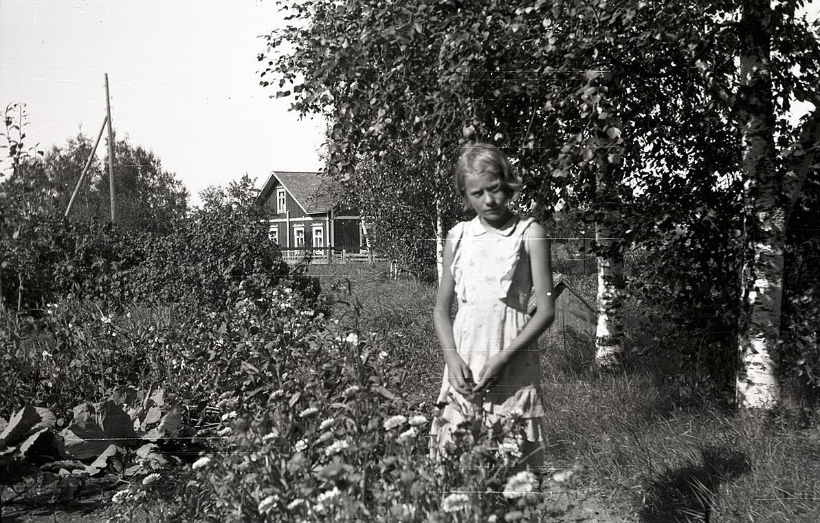 Karin Knus, som sedan gifte sig med Michael Mangs från Tjöck. I bakgrunden Emil Knuts gård.