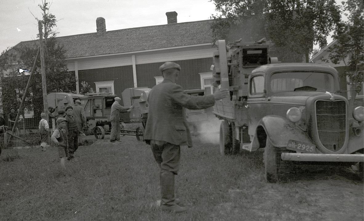 Frans Ånäs dirigerar lastbilarna med tröskverken till sina platser, medan småpojkarna står och ser på hur det skall lyckas.