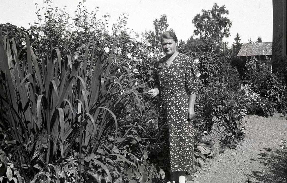 Eufrosyne Björses (1901-1949) var syster till fotografen och folkskolläraren Selim Björses, i vars trädgård hon står på fotot.
