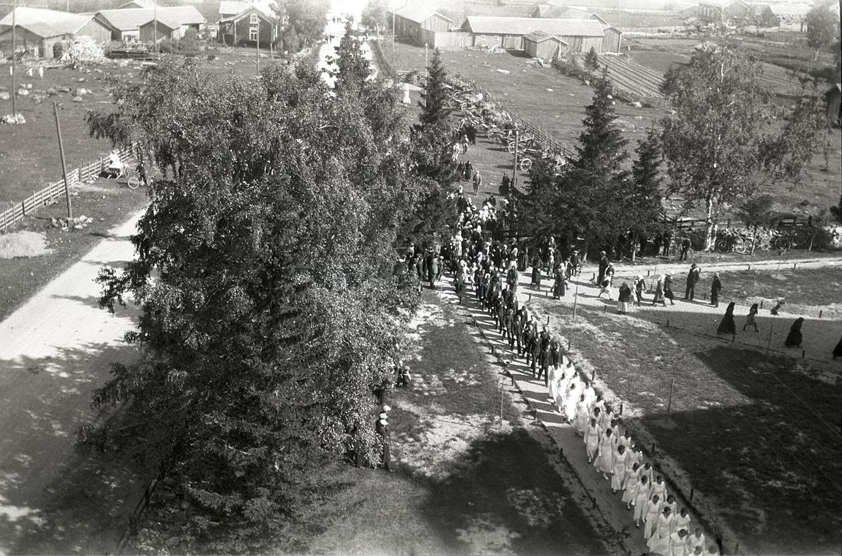 Lång rad med konfirmander på väg in i kyrkan midsommardagen 1939.