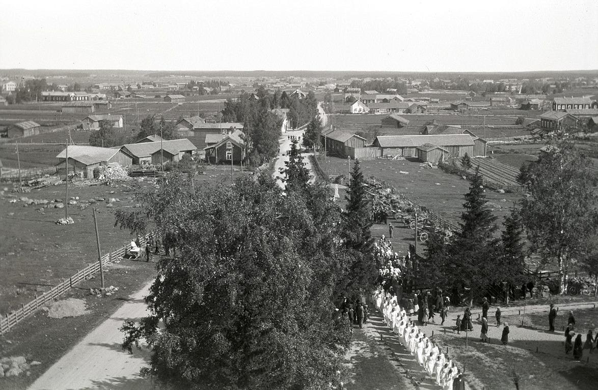 Skriftskolungdomarna på väg in i kyrkan. Notera raden med hästar till höger om paraden.