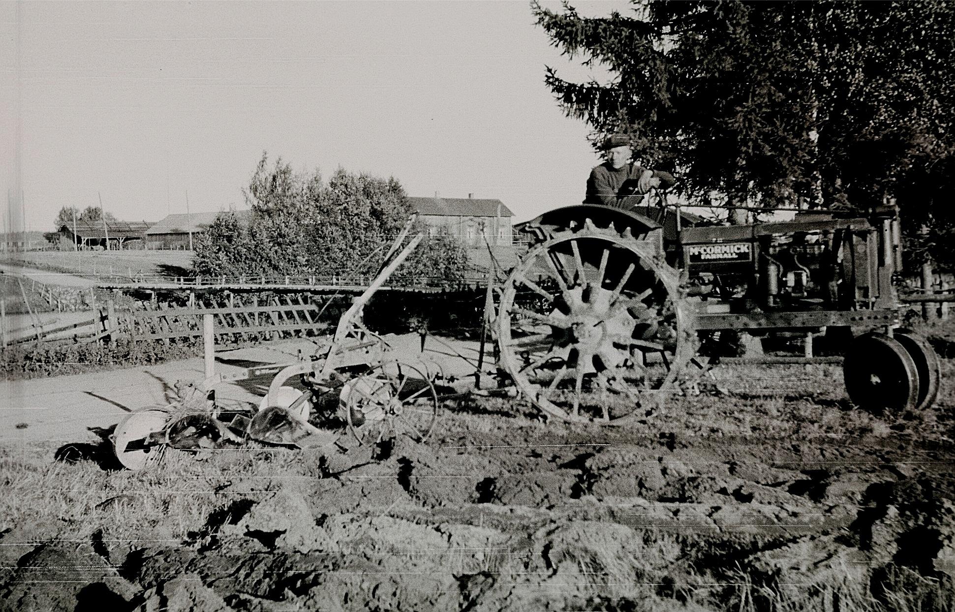 Otto Fröberg plogar med sin nya traktor av modell McCormick, med järnhjul både fram och bak. I bakgrunden Flottbron och Storhannus gård.