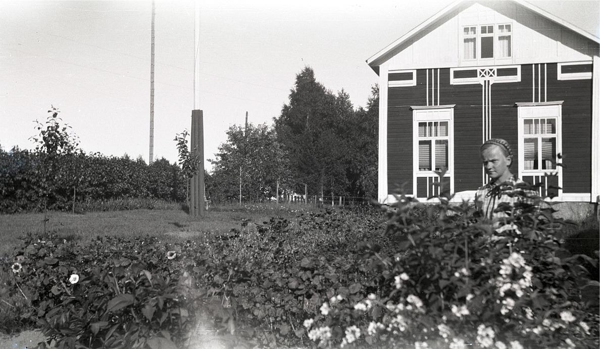 Verna Agnäs (f. 1925 senare gift med Arne Björkskog) visar upp sin fina trädgård, framför en minst lika fin bondgård på Sebbasbackan bredvid folkskolan i Dagsmark.
