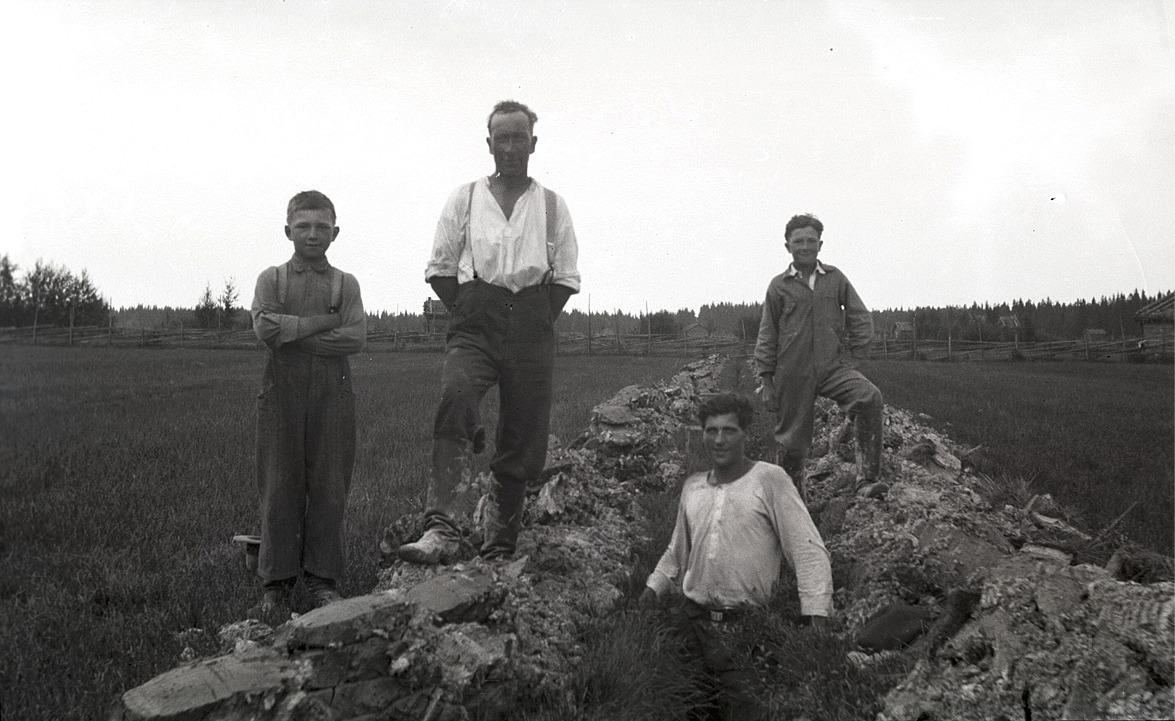 Till vänster Helge Holm (1927-2017) bredvid pappa Erland (1896-1950)och till höger står Olof Holm (f. 1925) och ser på då en okänd man håller på och täckdikar i åkern.