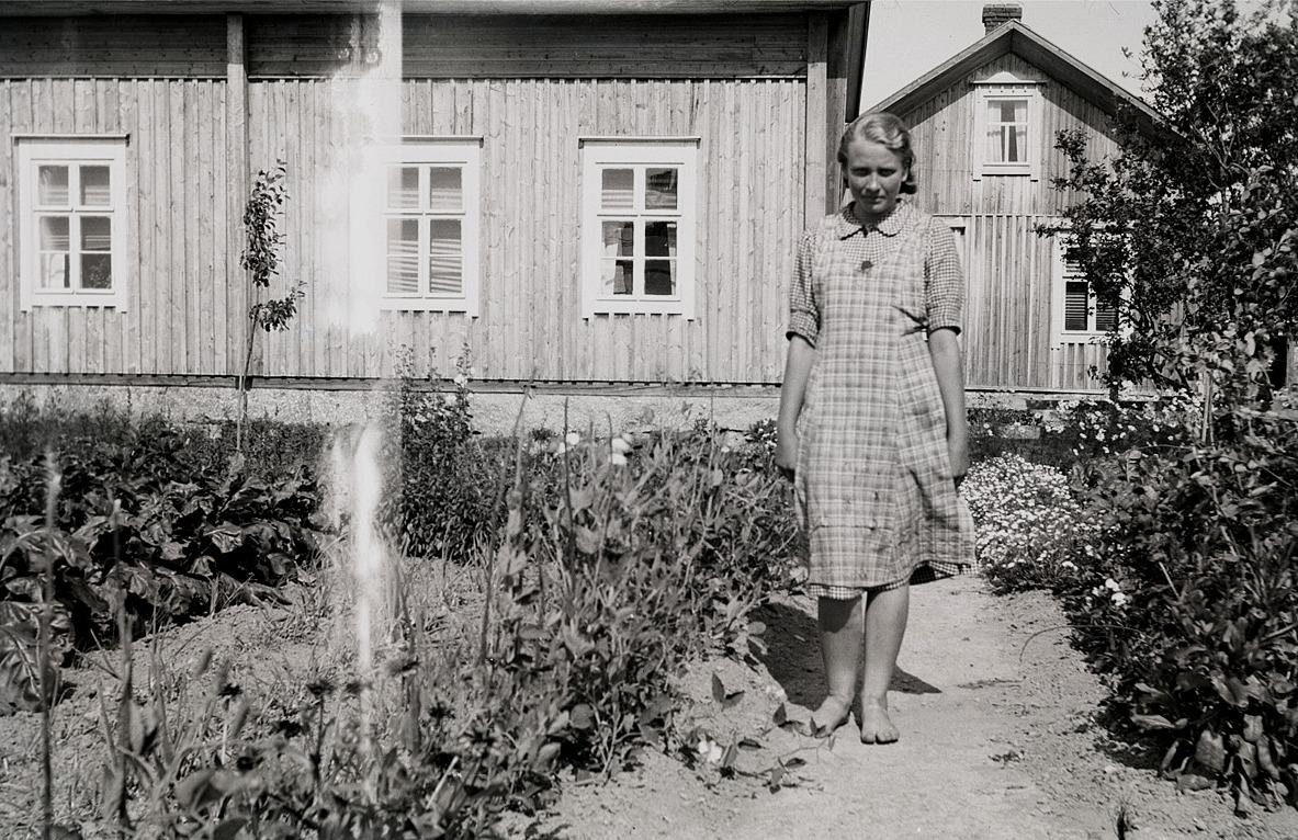 Greta Ebb (f. 1922, senare gift med Yrjö Sillanpää) i sin trädgård framför hemmet.