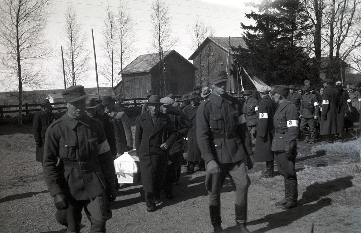 En stupad soldat bärs in i kyrkan av anhöriga, följd av skyddskårister och ett stort antal sörjande.