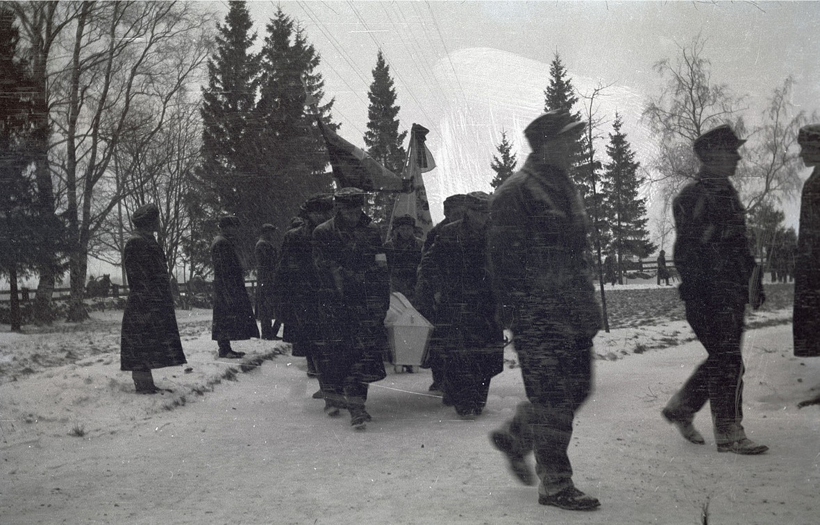 En stupad soldat bärs i snöyran in i kyrkan.
