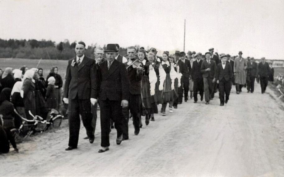 Här är Gunnar Guss på väg för att hämta bruden tillsammans med spelmän och bröllopsgäster. Mannen med hatten bredvid Gunnar är Bertel Långfors.