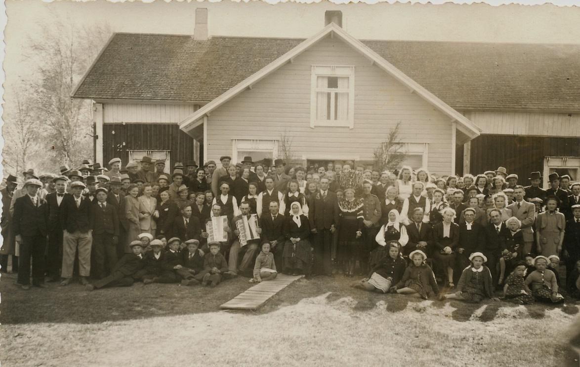 Gunnar och Svea Norrgård omgiven av släktingar och övriga bröllopsgäster framför Sveas hemgård i juni 1941.
