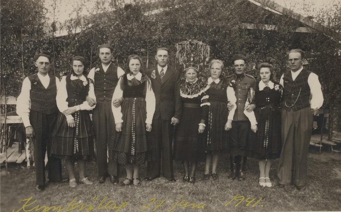 """Till vänster står """"Skomakas"""" Valter Rosenlund, född 1911 som stupade i fortsättningskriget i oktober 1941. Följande är """"Valentinas"""" Elin Rosenback (1913-1998), sedan följer brudgummens bror Eskil Guss (1917-1972) och sedan brudgummens syster Bertha, g. Ådjers (1923-1975). Bredvid bruden står hennes kusin Elvi Långfors (f.1919), i militärkläder står hennes kusin Eskil Norrgård (1919-1990), sedan kusin Florence Anderson (1916-1942) bredvid sin fästman Valter Rosengård."""