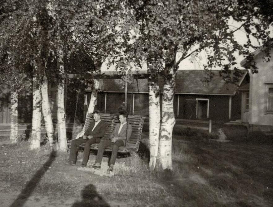 """Jörgen Norrgård (1944-1983) sitter i gungan tillsammans med """"Mattas-Jaal"""", alltså Jarl Grans (f.1944). Till höger skymtar Norrgårds lillstuga."""