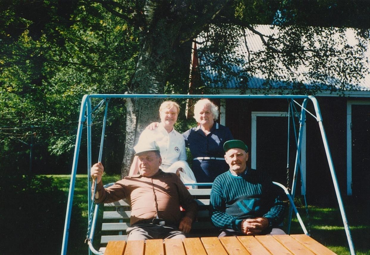Till höger sitter Gunnar Norrgård då han är och hälsar på sin granne Bertel Långfors. Bakom står Bertels hustru Julia med dottern Gretel till vänster.