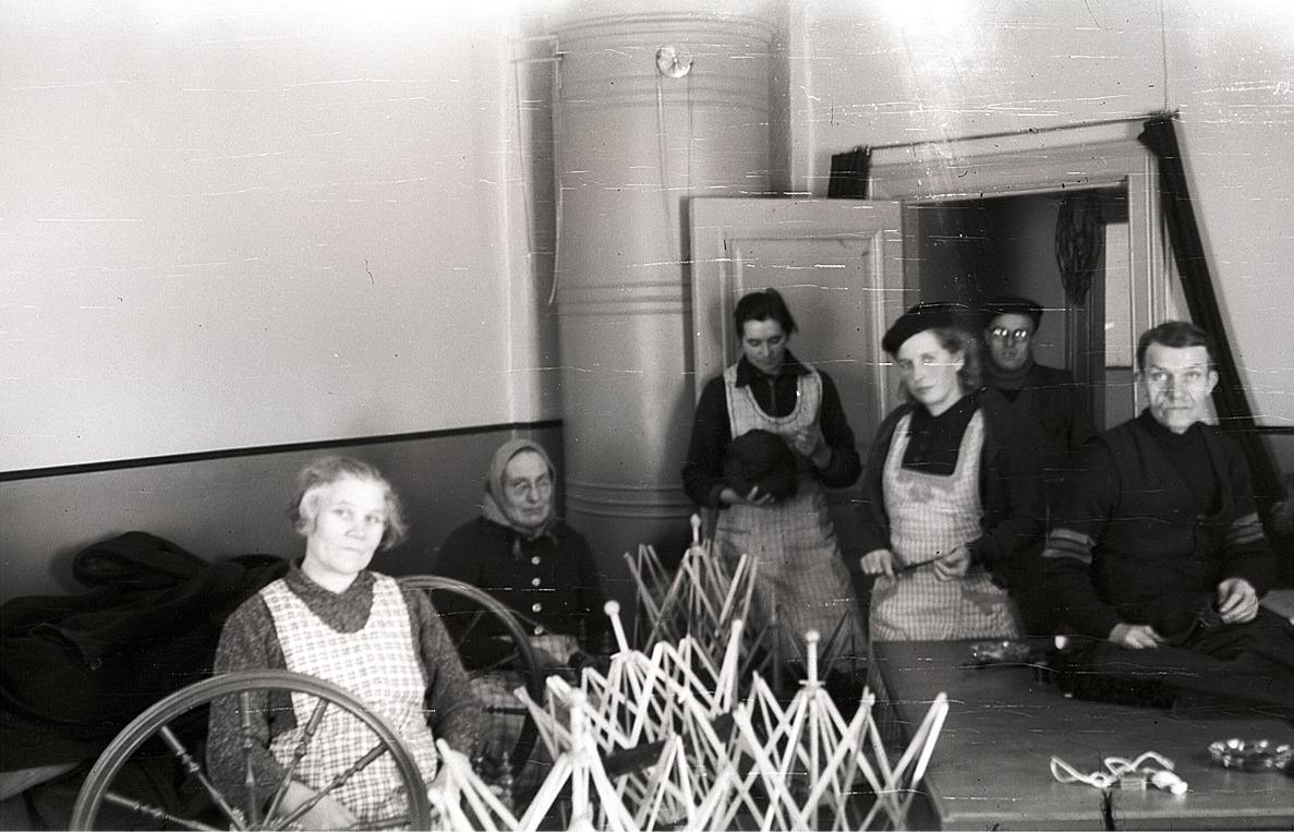 Här tillverkas kläder i arbetsstugan i centralcaféet för soldaterna ute vid fronten. Från vänster Sofia Rosenback, okänd, Hjördis Landgärds, Jenny Rosenback, Sigfrid Rosenback och mannen till höger okänd.