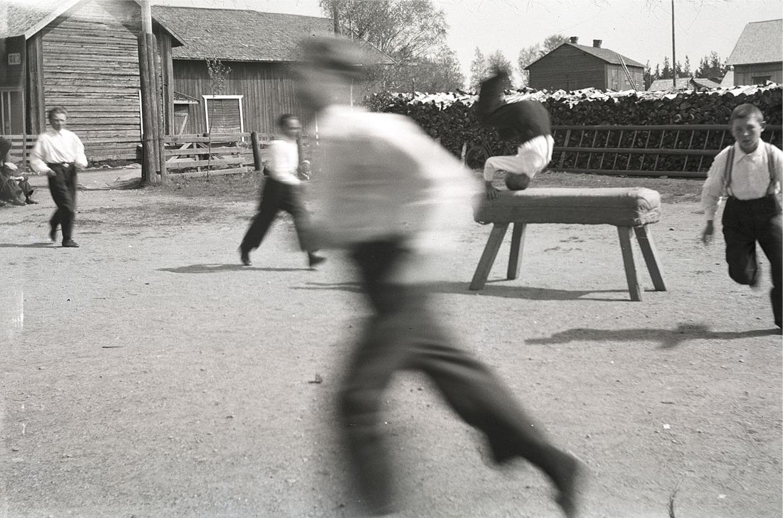"""Här hoppar elever kullerbytta över plinten på skolgården. Vedraden är så hög att """"Gustas Kaalas"""" skyms."""